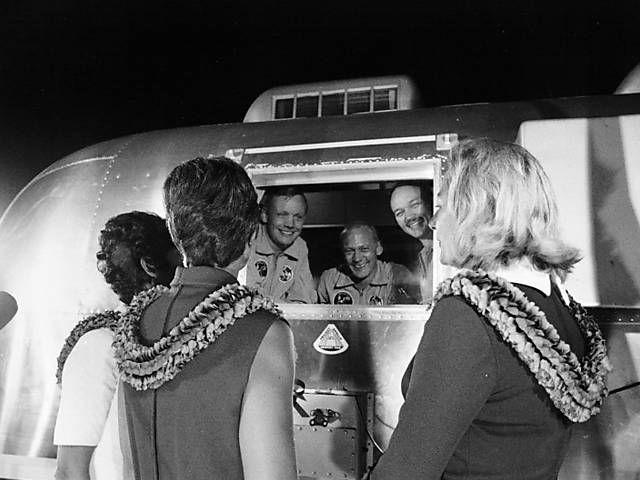 Mulheres dos astronautas esperam que eles saiam da cabine de quarentena na base aérea de Ellington_